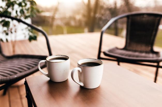 Dwie filiżanki kawy na stole na drewnianym brązowym tarasie podczas wieczornego zachodu słońca. koncepcja relaksu, kawiarni lub restauracji