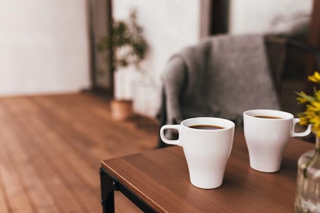 Dwie filiżanki kawy na stole na drewnianym brązowym tarasie podczas wieczornego zachodu słońca. relaks, cicha koncepcja życia na wsi. cudowne wieczory dla par