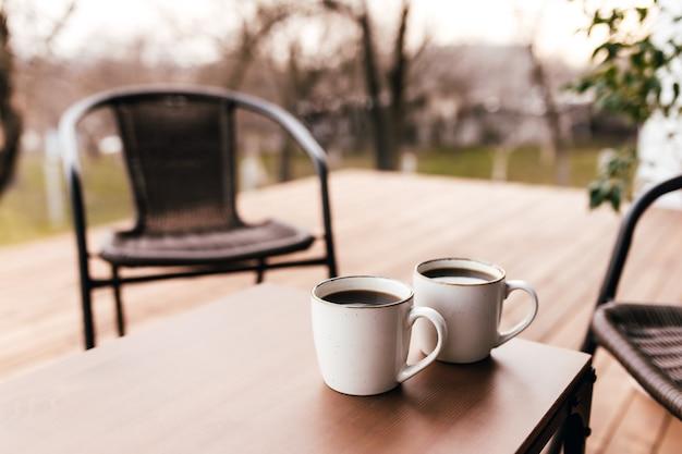 Dwie filiżanki kawy na stole na drewnianym brązowym tarasie podczas wieczornego zachodu słońca. relaks, koncepcja romantycznego wieczoru kochanków