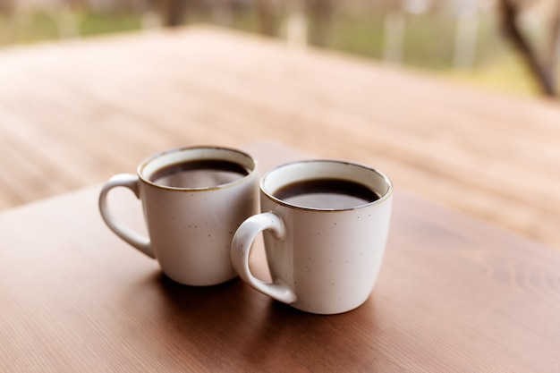 Dwie filiżanki kawy na stole na drewnianym brązowym tarasie. relaks, cicha koncepcja życia na wsi