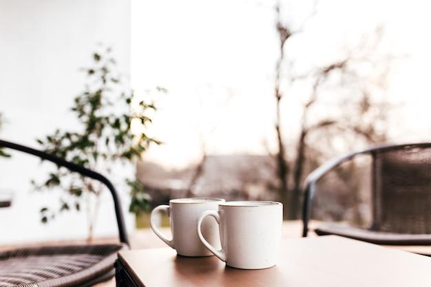 Dwie filiżanki kawy na stole na drewnianym tarasie brązowy podczas wieczornego zachodu słońca z rozmytym tłem. koncepcja relaksu, kawiarni lub restauracji