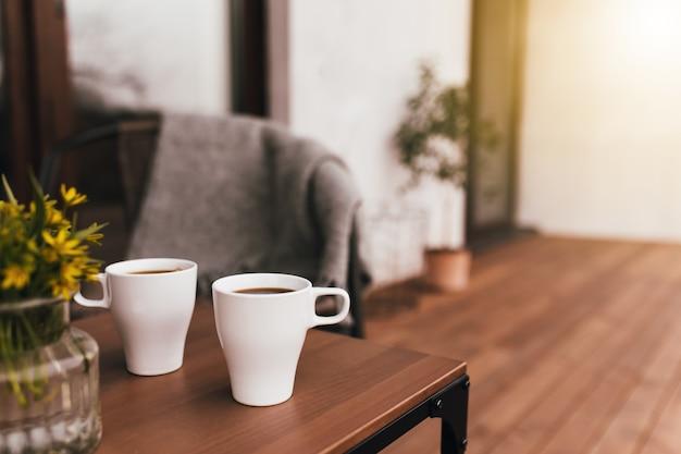 Dwie filiżanki kawy na stole na drewnianym tarasie brązowy podczas wieczornego zachodu słońca z rozmytym tłem. relaks, koncepcja życia cichej wsi. cudowne wieczory dla par?