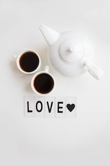 Dwie filiżanki kawy na stole z czajnikiem, napis love