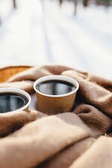 Dwie filiżanki kawy na szaliku w zaśnieżonym lesie.