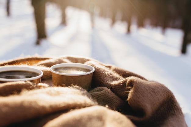 Dwie filiżanki kawy na szaliku w zaśnieżonym lesie