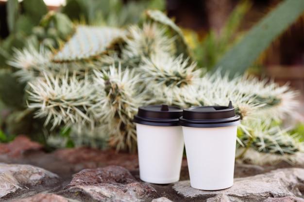 Dwie filiżanki kawy na wynos, filiżanki na białym papierze na kamieniach.