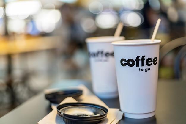 Dwie filiżanki kawy na wynos na stole w kafeterii.
