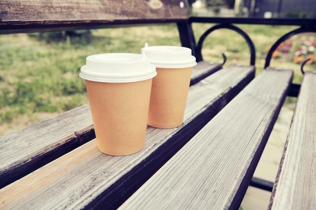 Dwie filiżanki kawy na wynos w parku na drewnianej ławce.