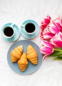 Dwie filiżanki kawy, rogaliki i bukiet różowych tulipanów, piękny poranek