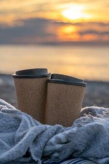 Dwie filiżanki kawy w kocu na plaży o zachodzie słońca