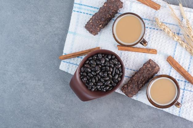 Dwie filiżanki kawy z kartką papieru i czekoladki na obrusie.
