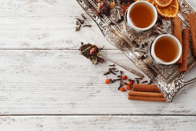 Dwie filiżanki parzonej herbaty z przyprawami na jasnym drewnianym stole