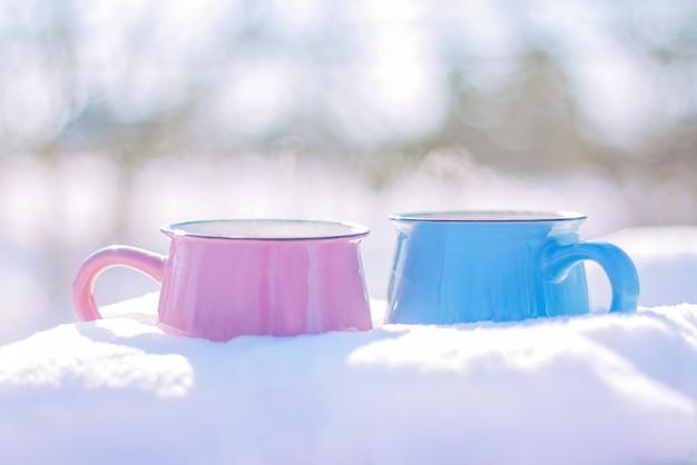 Dwie filiżanki stoją na śniegu w słoneczny zimowy dzień