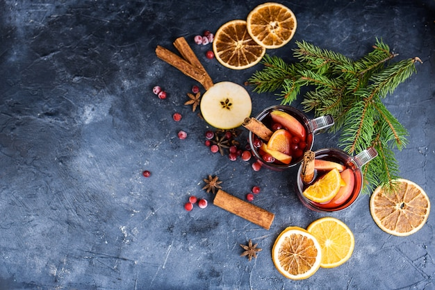 Dwie filiżanki świątecznego grzanego wina lub gluhwein z przyprawami i plasterkami pomarańczy na rustykalnym stole