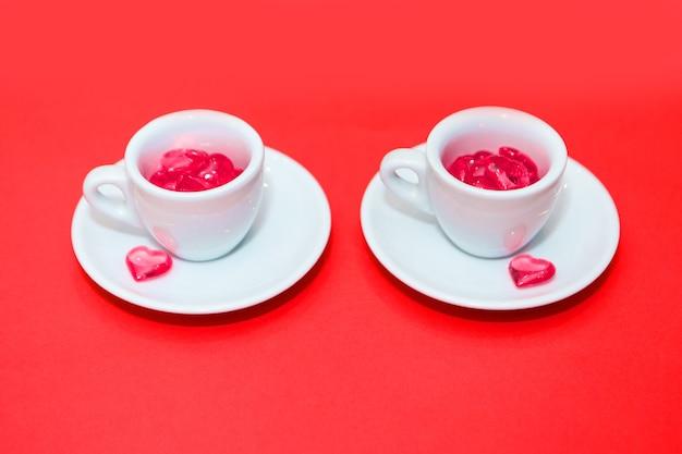 Dwie filiżanki z sercami na czerwonej powierzchni. widok z góry. wylały się czerwone serca. pojedynczo na różowym tle. skopiuj miejsce