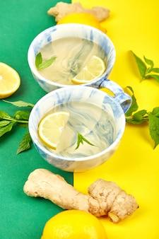 Dwie filiżanki zdrowej herbaty z cytryną, imbirem, miętą