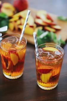 Dwie filiżanki żółtego soku brzoskwiniowego na drewnianym stole