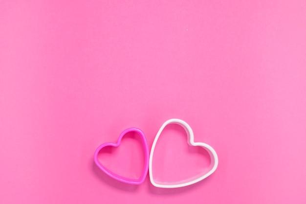 Dwie foremki do ciastek w kształcie serca na różowo
