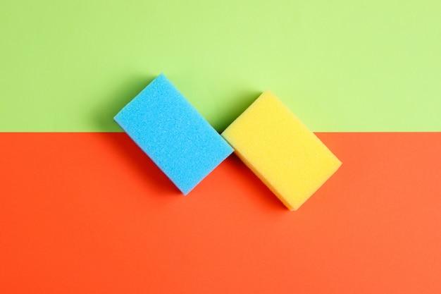 Dwie gąbki na kolorowym stoliku papierowym,