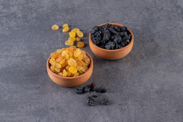Dwie gliniane miski z czarnymi i złotymi rodzynkami na kamiennym tle.