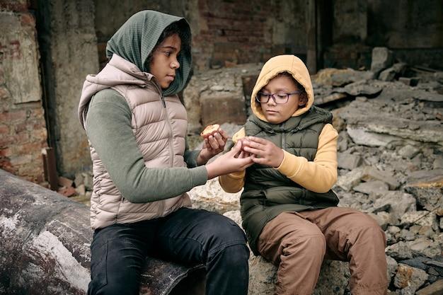 Dwie głodne dziewczyny dzielą się brzoskwinią siedząc na ruinach budynku