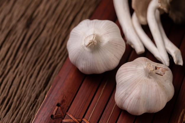 Dwie główki czosnku na drewnianych listwach i bajkowy grzybek
