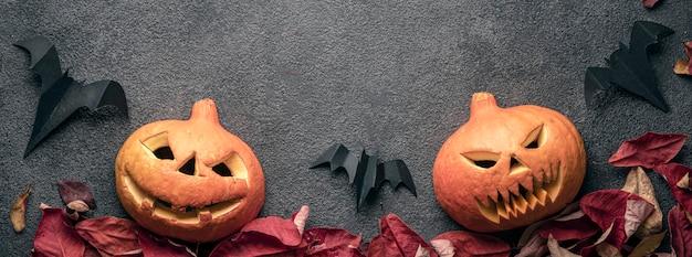 Dwie głowy dyni jack to przerażające, halloweenowe, panaramiczne zdjęcia. jesienne liście wakacyjne