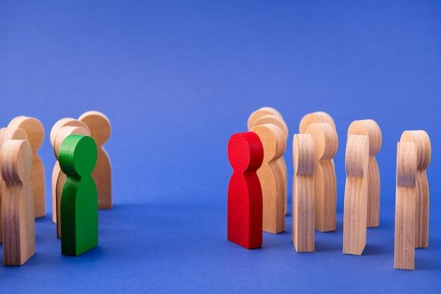 Dwie grupy drewnianych figurek stojących naprzeciwko siebie dyskutujących