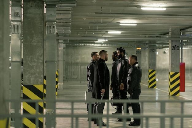 Dwie grupy międzykulturowych mężczyzn z pistoletami wchodzącymi w interakcję stojąc naprzeciw siebie na parkingu