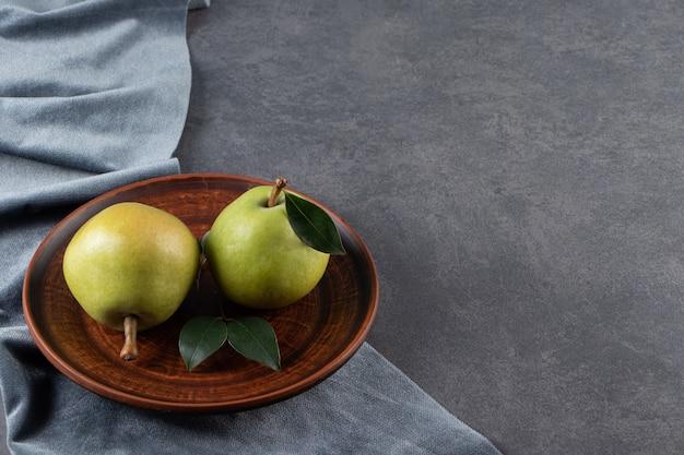 Dwie gruszki na drewnianym talerzu na kawałku materiału na marmurowej powierzchni