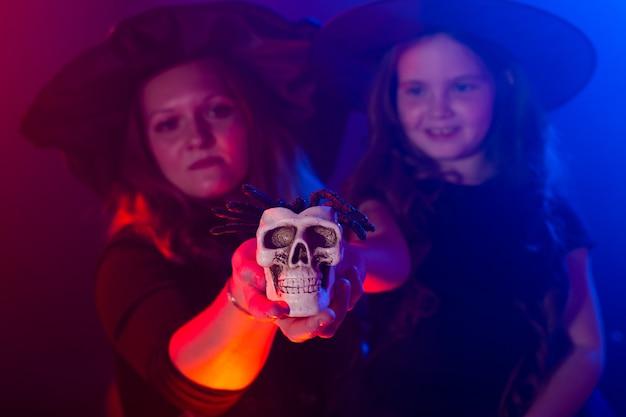 Dwie halloweenowe czarownice robiące magię z czaszką w halloweenowych nocnych magicznych świętach i mistycznej koncepcji