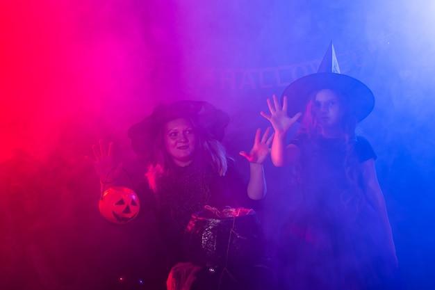 Dwie halloweenowe wiedźmy robią miksturę i wyczarowują w halloweenowej nocy magiczne święta i mistyk