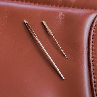Dwie igły na brązowej skórze z ręcznie robionymi szwami