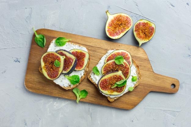 Dwie kanapki z twarogiem, figami, sałatką z miodu i liści na drewnianej desce rustykalnej na szaro