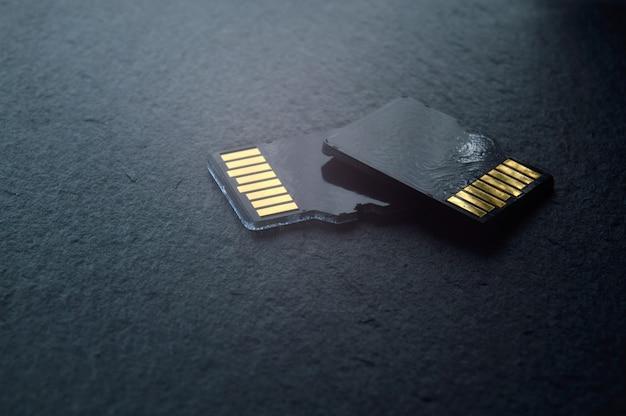 Dwie karty micro sd leżą jedna na drugiej na ciemnym tle z teksturą, ze złotymi stykami u góry. zbliżenie.