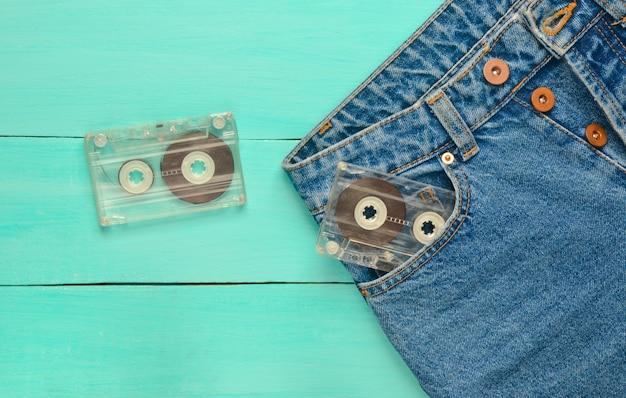 Dwie kasety audio w kieszeni jeansów na niebieskiej drewnianej powierzchni. technologia mediów z lat 80.