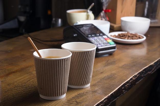 Dwie kawy w rzemieślniczym kieliszku i terminal płatniczy