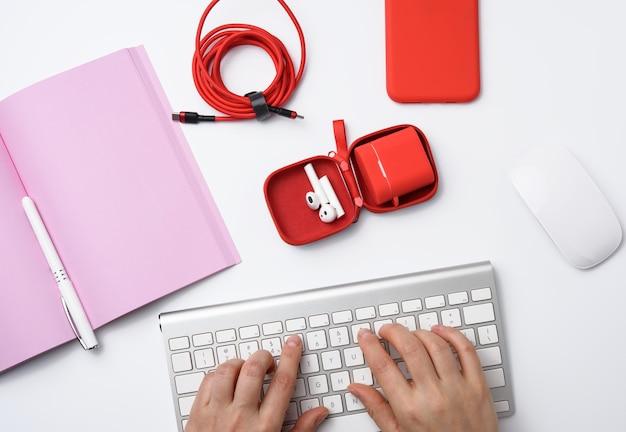 Dwie kobiece dłonie i biała klawiatura, miejsce pracy freelancera z otwartym notebookiem, słuchawki, czerwony smartfon, biały stół, widok z góry