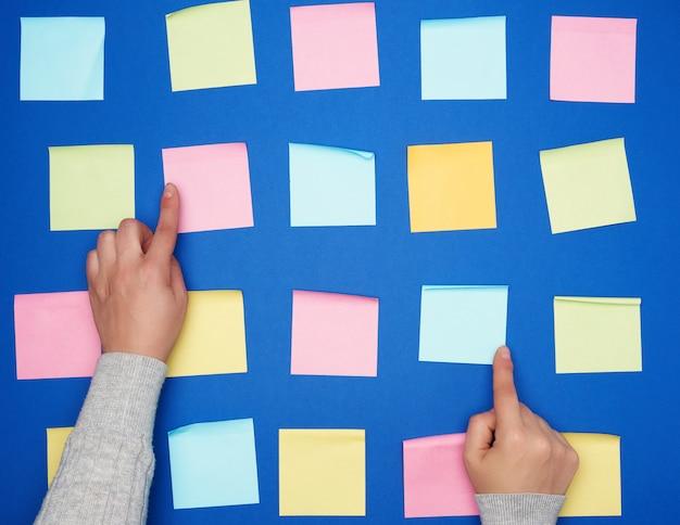 Dwie kobiece dłonie i dużo pustych papierowych kolorowych kwadratowych naklejek na niebieskim tle