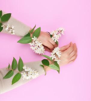 Dwie kobiece dłonie i małe białe kwiaty