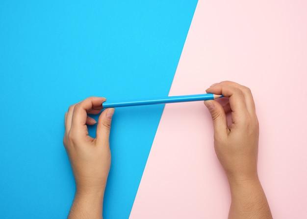 Dwie kobiece dłonie trzymają niebieski drewniany ołówek, widok z góry