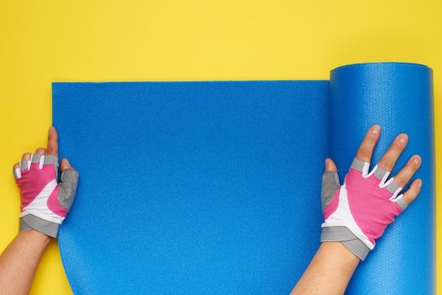 Dwie kobiece dłonie w sportowych rękawiczkach rozkładają niebieską matę do jogi