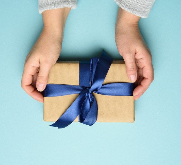 Dwie kobiece dłonie w swetrze trzymają kwadratowe pudełko z niebieską kokardą na niebieskim tle, widok z góry, świąteczne tło