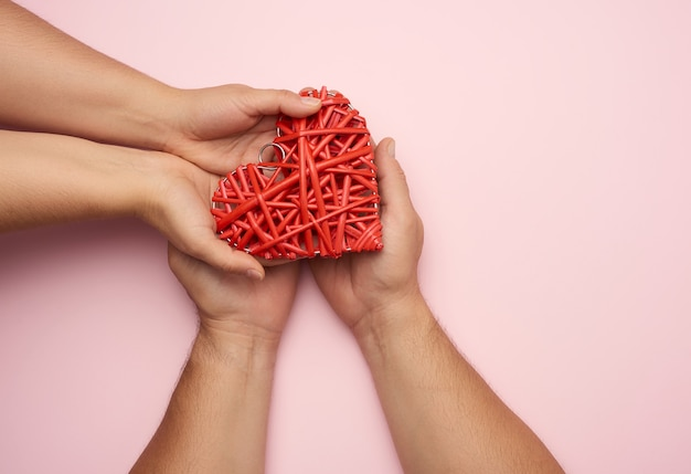 Dwie kobiece dłonie wkładają czerwone serce w dłonie mężczyzn. pojęcie dobroci, darowizny, widok z góry