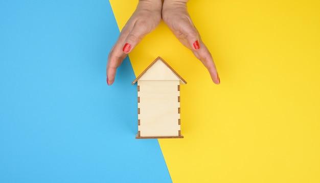Dwie kobiece dłonie złożone do siebie nad drewnianym miniaturowym modelowym domem na żółtym tle