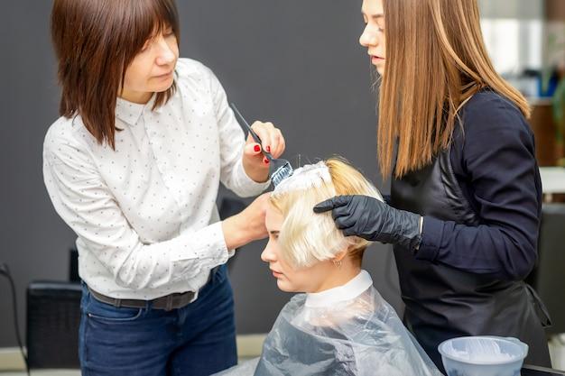 Dwie kobiece fryzjerki farbowania włosów młodej kobiety rasy kaukaskiej w salon fryzjerski
