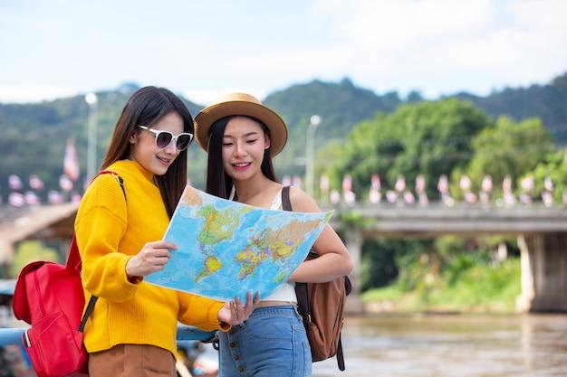 Dwie kobiece turystki trzymają mapę, aby znaleźć miejsca.