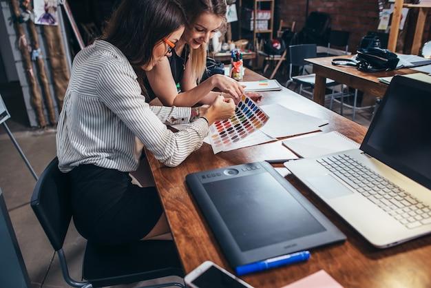 Dwie kobiety architektów pracujących razem przy użyciu próbek kolorów, siedząc przy biurku z laptopem, tabletem graficznym w studio projektowym.