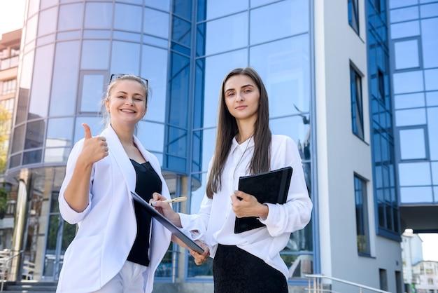 Dwie kobiety biznesu podpisują umowę na zewnątrz przed budową dużego centrum biurowego