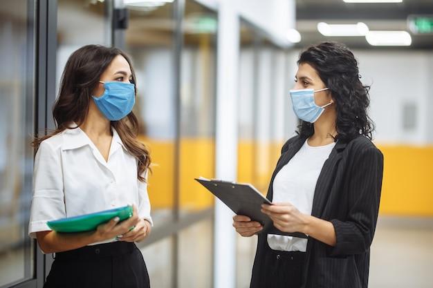 Dwie kobiety biznesu rozmawiają o sprawach roboczych w biurze w sterylnych maskach medycznych. nowa koncepcja środków normalnych, ochrony zdrowia i środków bezpieczeństwa.